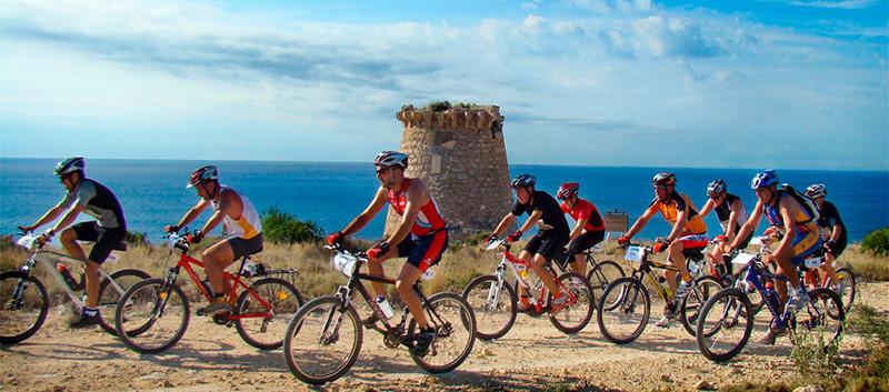 ciclistas en la sierra de santa pola. Se ve la torre de Escaletes